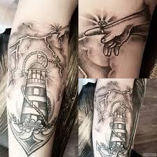 молния с маяком и якорем тату на предплечье у парня добавлено