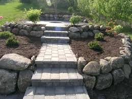 paver patio with fireplace custom build brick steps and walkway leading to outdoor wood burning surrounded by blooming plants in raised boulder planters