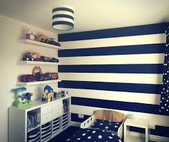 nautical themed toddler bedroom showing a navy and white striped wall navy and white lampshade