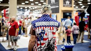 an attendee wears an an american flag shirt depicting president donald as the terminator during