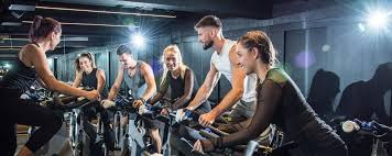 spinning instructor guiding gym members in cycling group