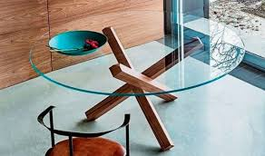 a clear round glass top and wooden legs that remind of usual firewood looks cool and