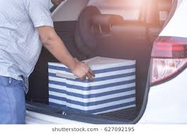 man loading box into car
