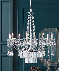 a crystal chandelier hangs in a teal room