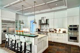 white kitchen with raised glass breakfast bar and slate floor tiles