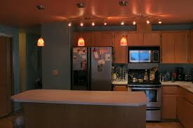 kitchen recessed lighting design with wooden kitchen cabinet and gray colored kitchen backsplash also three