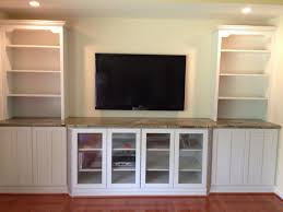 floating white wooden shelves on the white wall plus television on the middle combined with white