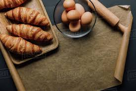 Flat Lay With Eggs In Bowl Tray With Croissants Rolling Pin And