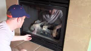 how open remove to clean the glass cover on a gas fireplace