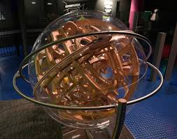 large sphere suspended in a frame with a wooden 3d maze inside