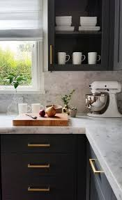 dark gray cabinets with marble countertops and backsplash