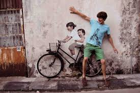 ernest with the children passing through on famous wall art in penang with little children on a bicycle mural armenian street george town
