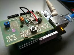 in the picture is the pcb from the inside of a traditional garage door opener is laid on top of the ethernet shield arduino uno combo