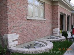 pretty egress window wells with brick siding and retaining wall for home exterior design ideas