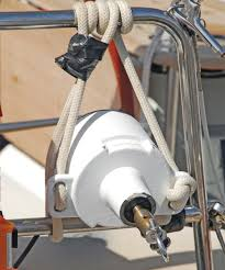 a transom mounted water turbine drags a spinning propeller behind the boat to generator power