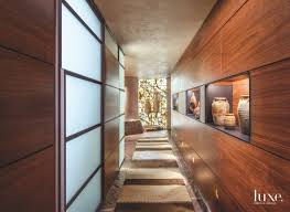 one of the main hallways of this home is lined with walnut paneling a runner from azadi fine rugs and antique pottery including 16th century pieces from