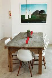 Contemporary farmhouse table with modern chairs milk bottle lights, white  eames style chairs and rustic