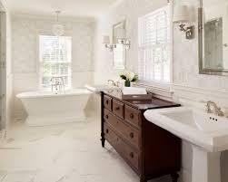 Elegant freestanding bathtub photo in Milwaukee with a pedestal sink,  raised-panel cabinets,