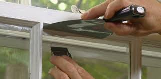 sing dried paint off window pane using razor blade glass ser and putty knife