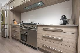 the wood grain kitchen cabinets add texture and warmth to this modern gloss kitchen