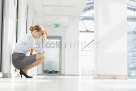 office hallway. Full-length Side View Of Stressed Businesswoman Crouching At Office Hallway Stock Photo V