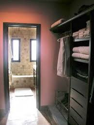 master bedroom with bathroom and walk in closet. is that a dusty pink closet w/ dark brown trim? walk through to bath bedroom master with bathroom and in