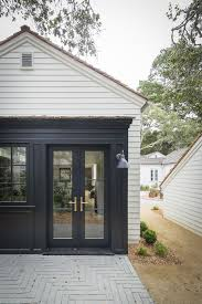 the private back patio with doors painted in sherwin williams greenblack for contrast