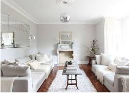 living room two couches. living room in a uk country house with walnut herringbone wood floors, white sofas, molded fireplace, gray walls, and shag rug long two couches e