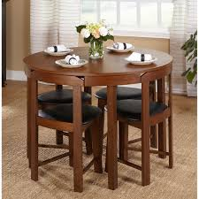 The Tobey Compact Dining Set by Simple Living offers four chairs that fit  perfectly under the round table ideal for a small dining space or living  area.