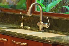 porcelain undermount sink in green granite countertop with instant hot water faucet