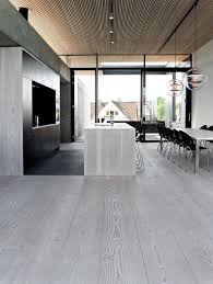 modern kitchen with grey wood floors going up to the walls and the kitchen island