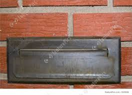 an old mail slot in a brick wall