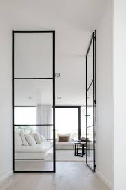 floor to ceiling black framed glass doors look perfect in a neutral modern ambience