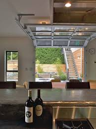 a glass paneled garage door virtually eliminates the division between the main room and an