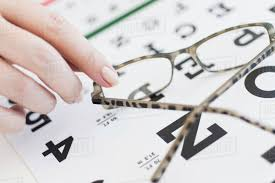 Close Up Of Womans Hands Holding Glasses Above Eye Chart D1028_32_498
