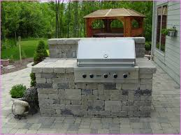 outdoor grill station ideas with decorative plants on stone flooring