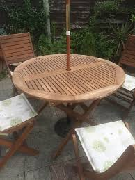 used wooden garden furniture set including table four chairs with cushions parasol and stand