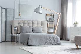 this is another room that has that modern industrial look to it the walls and floor are grey and there s a huge floor lamp set above the bed