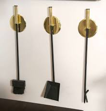 for on rare set of three brass mid century fireplace tools comprised of 3 discs brackets that mount to wall each separately holding a fire tool