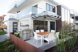 white striped patio umbrella: california beach style patio features a white dining table surrounded by white modern dining chairs shaded by a black and white striped umbrella while a