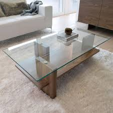 Modern design with glass tabletop and solid wood frame, providing elegant style and durability. 29 Chic Glass Coffee Tables That Catch An Eye Digsdigs