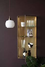 lifestyle image of the brass glass wall mounted display cabinet with pendant light