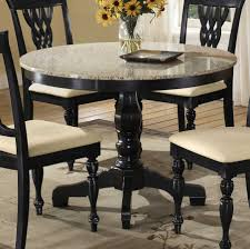 36 inch round pedestal dining table with wooden base painted with black color and marble top plus 4 chairs with white cushions on carpet tiles
