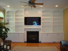 Arch face top, base cabinets, crown moulding, bookcases frame the ...