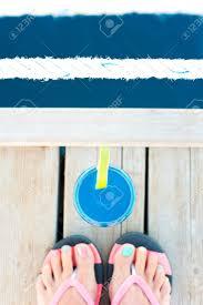 新鮮な柔らかいカクテルを飲むに近い木造の桟橋の上に色のペディキュア
