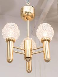 a chic mid century modernist three arm brass chandelier with relief glass globes