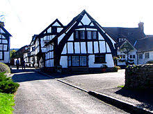 a true or full cruck half timbered building in weobley herefordshire england the cruck blades are the tall curved timbers which extend from near the