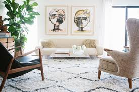 a modern eclectic living room with large art and moroccan rug via coco kelley