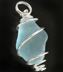 aqua blue sea glass is wrapped in a sy spiral pendant ready to hang on your favorite chain