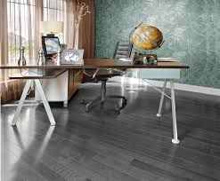 grey bamboo hardwood flooring with small wooden office table and black leather wheeled chair near large window